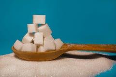 Açúcar em uma colher de madeira na tabela Foto de Stock