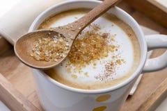 Açúcar mascavado em uma colher e em um cappuccino da xícara de café Fotografia de Stock