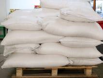 Açúcar nos sacos, empilhados na pálete de madeira imagem de stock