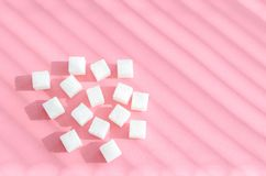 Açúcar refinado no fundo cor-de-rosa Cubos do açúcar doce e branco no geometricshape Sombras duras imagem de stock royalty free