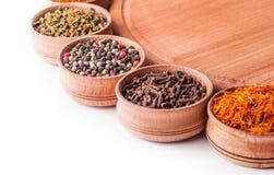 Açafrão, cravos-da-índia, paprika em uma bacia de madeira Imagem de Stock