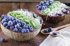 Açai Bowls with Kiwi Coconut Chocolate and Frozen Berries stock photos
