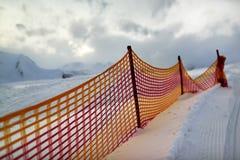 Açaime a grade vermelha em uma inclinação do esqui na noite Fotografia de Stock Royalty Free