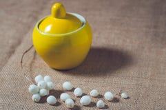 Açucareiro amarelo em uma tabela com bolas brancas Fotografia de Stock