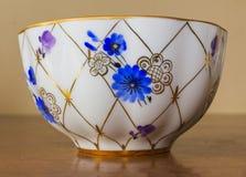Açucareiro da porcelana, copo, leite, prato com teste padrão dourado e flores azuis imagem de stock royalty free