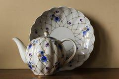 Açucareiro da porcelana, copo, leite, prato com teste padrão dourado e flores azuis imagens de stock royalty free
