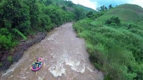 Aéreo - el barco el transportar en balsa de Whitewater sigue el río del tiro abajo en Tailandia almacen de video
