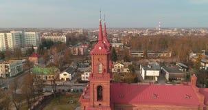 aéreo El punto del abejón del interés 360 tiró iglesia del ` s de San Pedro y de Paul en Panevezys Tarde de la primavera en Litua almacen de metraje de vídeo