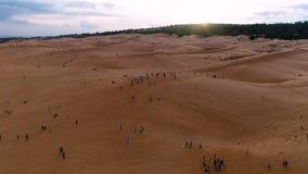 aéreo El tiro inclinable del abejón de la revelación de la gente viene ver la puesta del sol y tener atracciones en las dunas de  metrajes