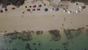 Aéreo, gente y paraguas del colorfull en la playa metrajes