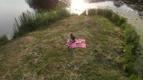 Aéreo: Mãe nova com suas filhas do bebê em um piquenique em um parque - zangão morno da cena do verão da cor dos valores familiar filme
