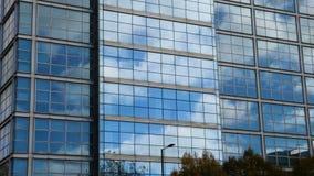 aéreo Movimento suave da câmera na frente das janelas do prédio de escritórios que refletem o céu azul ensolarado com as nuvens i filme