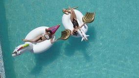 Aéreo - mujer atractiva joven en el bikini que flota en un colchón de aire en la piscina el tomar el sol atractivo de las muchach metrajes