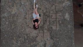 A?reo: Mujer tur?stica que se relaja en una roca - sensaciones calientes del viajero joven del verano - el llevar cauc?sico calie almacen de metraje de vídeo
