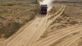 Aéreo para dos hombres en el camión rojo grande que conduce en el camino seco del campo con las nubes de la escena del polvo Cami almacen de metraje de vídeo