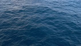 Aéreo - remate abajo de vista de una superficie de ondulación del agua del mar azul profundo almacen de video