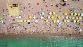 Aéreo: vista superior de la playa La gente se baña en el mar, en los parasoles de playa de madera de la orilla almacen de video