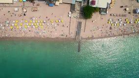 Aéreo: vista superior de la playa La gente se baña en el mar, en los parasoles de playa de madera de la orilla almacen de metraje de vídeo