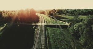 aéreo Voo da câmera das trilhas do trem ao filtro alto do céu do por do sol do verão adicionado 4K vídeos de arquivo