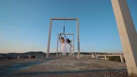 Aérez la femme de gymnastique accrochant sur le cercle aérien sur le toit avec une vue gentille clips vidéos