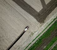 Aérez la vue de labourer le tracteur rouge sur le champ Image libre de droits