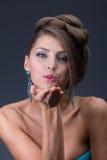 Aérez le baiser de la femme utilisant la boucle d'oreille bleue brillante Photo stock