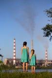 aérez le contrat à terme de concept de cheminée de soin ses gosses regardant des tiges de pollution de mère jeunes Photographie stock