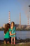 aérez le contrat à terme de concept de cheminée de soin ses gosses regardant des tiges de pollution de mère jeunes Images stock