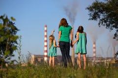 aérez le contrat à terme de concept de cheminée de soin ses gosses regardant des tiges de pollution de mère jeunes Photos libres de droits