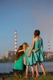 aérez le contrat à terme de concept de cheminée de soin ses gosses regardant des tiges de pollution de mère jeunes Photographie stock libre de droits