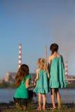 aérez le contrat à terme de concept de cheminée de soin ses gosses regardant des tiges de pollution de mère jeunes Images libres de droits