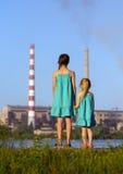 aérez le contrat à terme de concept de cheminée de soin ses gosses regardant des tiges de pollution de mère jeunes Image libre de droits