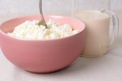 Aérez le fromage blanc avec la cuillère dans un plat et un verre profonds de lait Photographie stock libre de droits