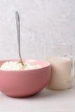 Aérez le fromage blanc avec la cuillère dans un plat et un verre profonds de lait Images stock