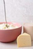 Aérez le fromage blanc avec la cuillère dans un verre profond de plat de lait Photo libre de droits