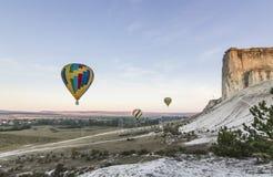 Aérez les baloons au lever de soleil près de la grande roche blanche Photo libre de droits