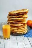 Aérez les gâteaux plats savoureux avec du jus frais orange Photographie stock libre de droits