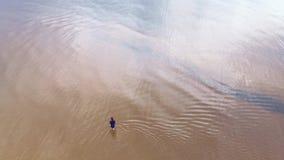 Aérien : jeune femme dans la robe lumineuse bleue marchant autour - du paysage jaunâtre scénique de coucher du soleil d'eau peu p banque de vidéos