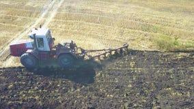 Aérien - tracteur avec la charrue de quatre sillons labourant un champ banque de vidéos