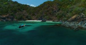 Aérien : Un bateau solitaire de longtail se tient près de la plage avec de l'eau turquoise banque de vidéos