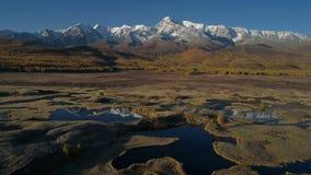 aérien Voler au-dessus du beau lac près des montagnes Automne, arbres d'or banque de vidéos