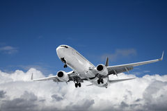 Aéronefs commerciaux au-dessus de ciel bleu et de cumulus Photographie stock libre de droits