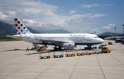 Aéroport de Dubrovnik avec le jet et le chariot à bagages Image stock