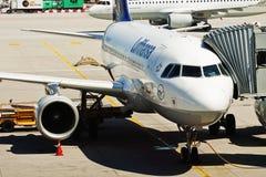 Aéroport de Munchen : avion avec le pont d'embarquement de passager Photographie stock