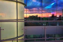 Aéroport et ciel de coucher du soleil reflété dans les fenêtres Image stock