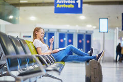 Aéroport international de jeune travelerin vérifiant son téléphone portable tout en attendant son vol Photo stock