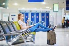 Aéroport international de jeune travelerin vérifiant son téléphone portable tout en attendant son vol Images stock