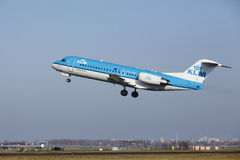 Aéroport Schiphol d'Amsterdam - le Fokker 70 de KLM Cityhopper décolle Image libre de droits