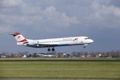 Aéroport Schiphol d'Amsterdam - terres du Fokker 100 d'Austrian Airlines Image libre de droits