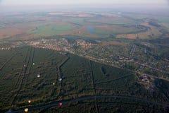 Aérostats dans le ciel au-dessus des champs et de la rivière. Photographie stock libre de droits